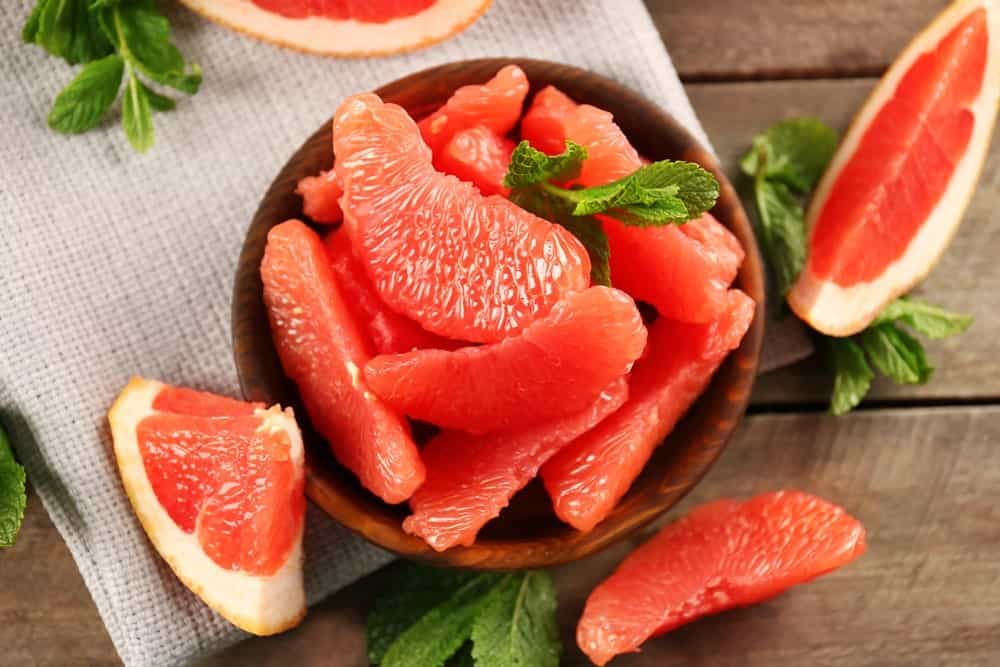 Slices of grapefruit in a wooden bowl against wood plank table.