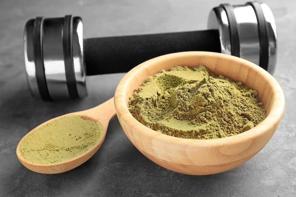 A wooden scoop and bowl of hemp protein powder beside a barbel.