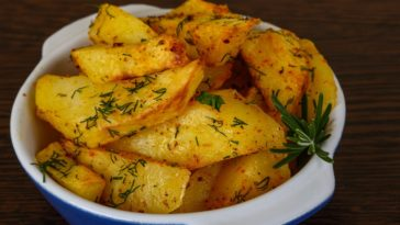 A bowl of herb roasted parmesan potatoes.
