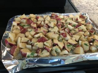 The seasoned and herbed potatoes are placed evenly on a baking pan.