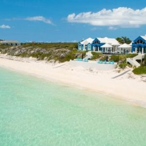 This is an aerial view of the beachfront mansion with brilliant white and blue tones to its exteriors to make it stand out against the surrounding landscape. Image courtesy of Toptenrealestatedeals.com.