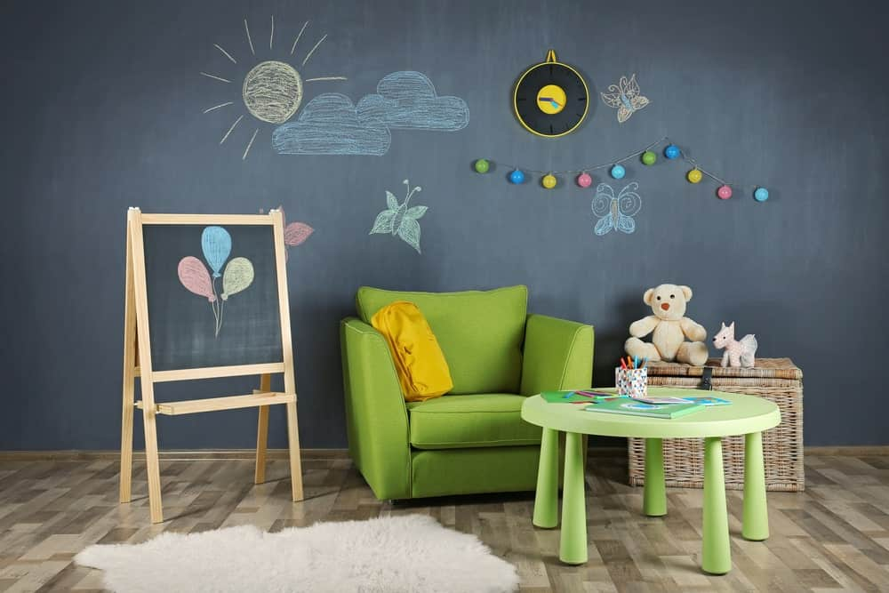 Kid's room with green armchair, round table, hardwood flooring, rattan toy storage, an a chalkboard wall.