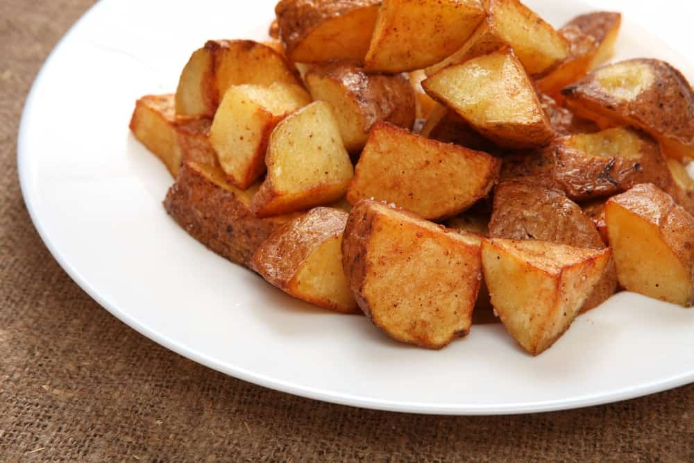 Home fries served on a white plate.