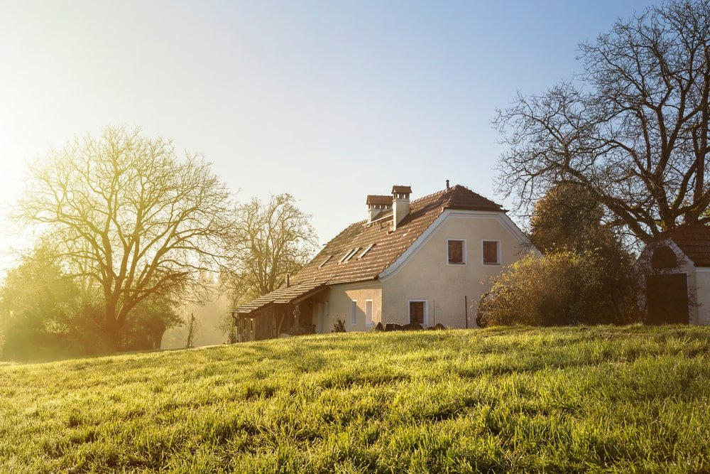 A house in the country surrounded by greenery.