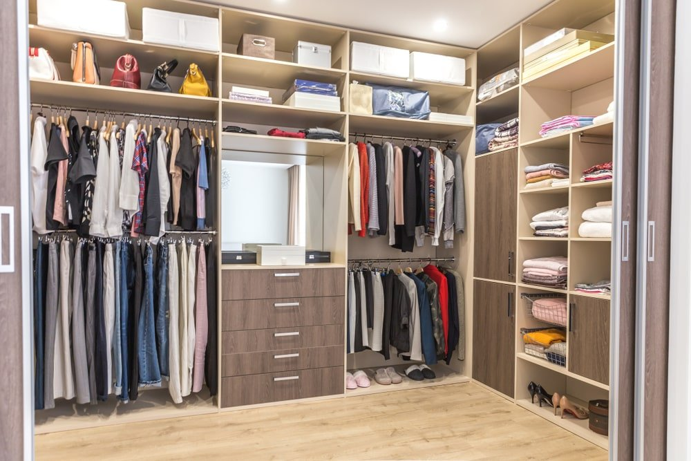 This is a spacious walk-in closet with built-in shelves, drawers and racks on its walls.
