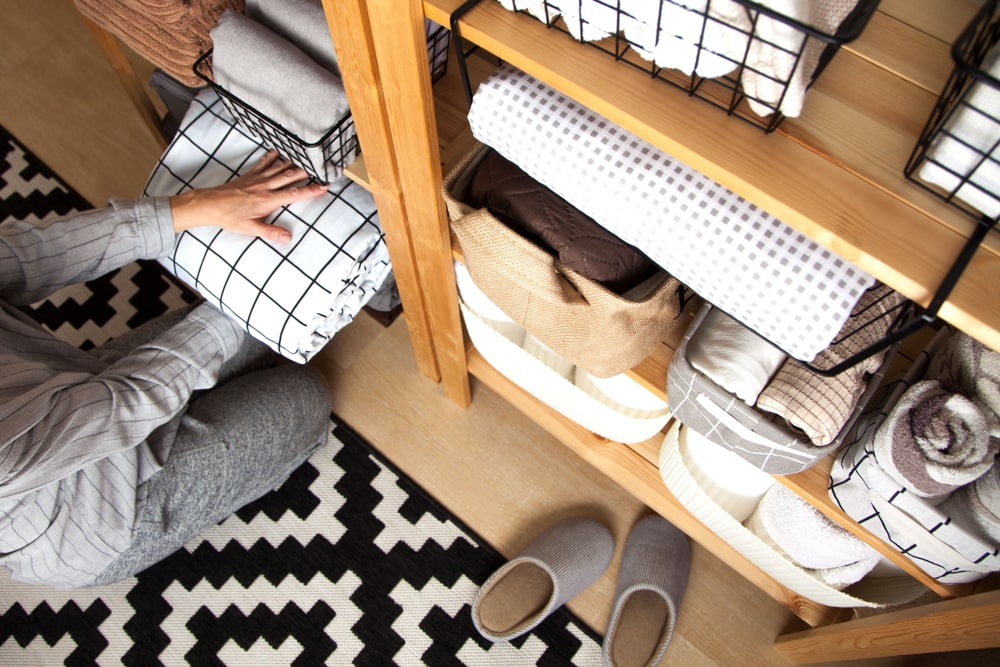 A woman organizing the contents of the wooden shelves.