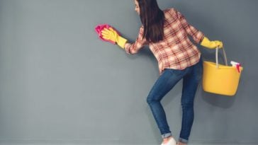 A woman scrubbing the gray wall with a rag.