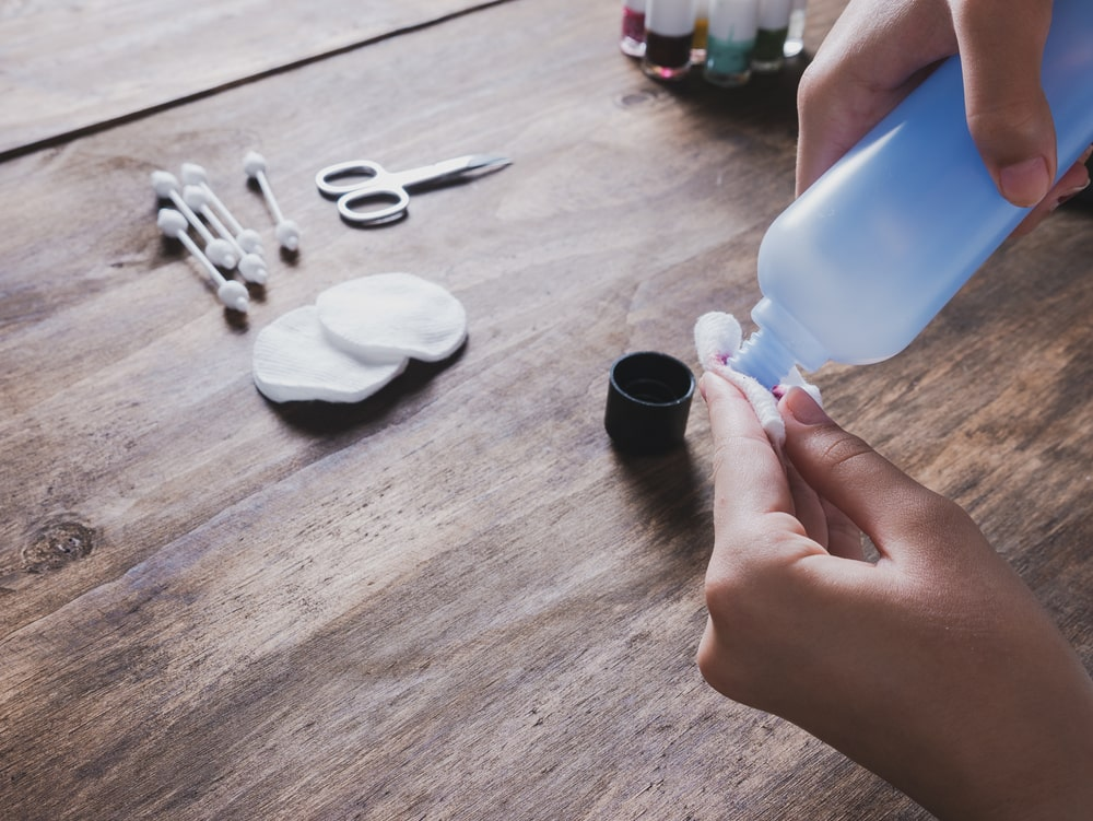 A woman pouring acetone on a piece of cotton.