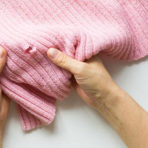 Close inspection of a moth-eaten knitted garment.