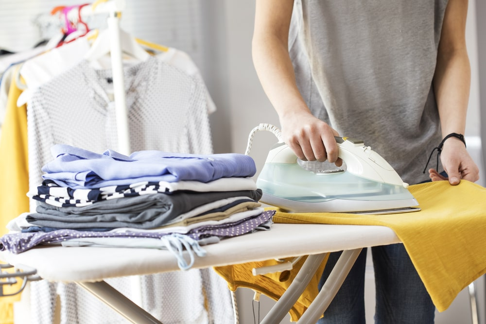 A person ironing clothes on ironing board.