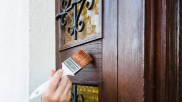 A person painting the wooden front door with a paintbrush.