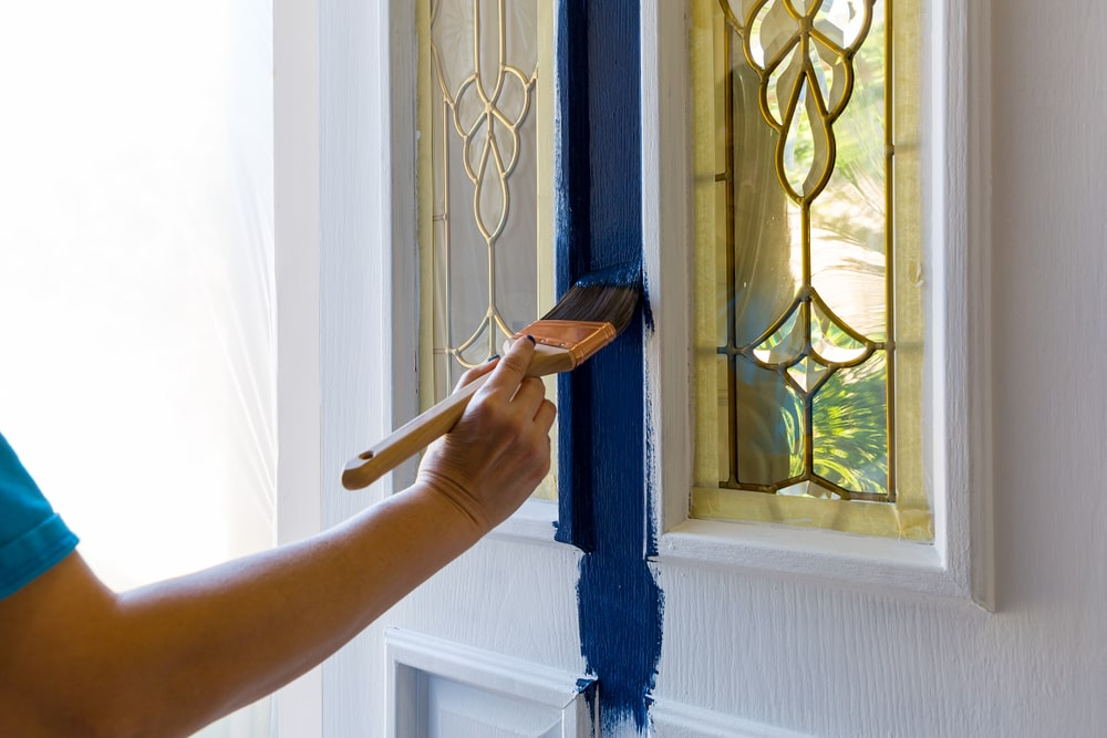 A person painting the white front door with blue paint using a paintbrush.