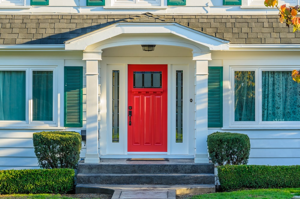 A look at this house's main entrance with a bright red door.