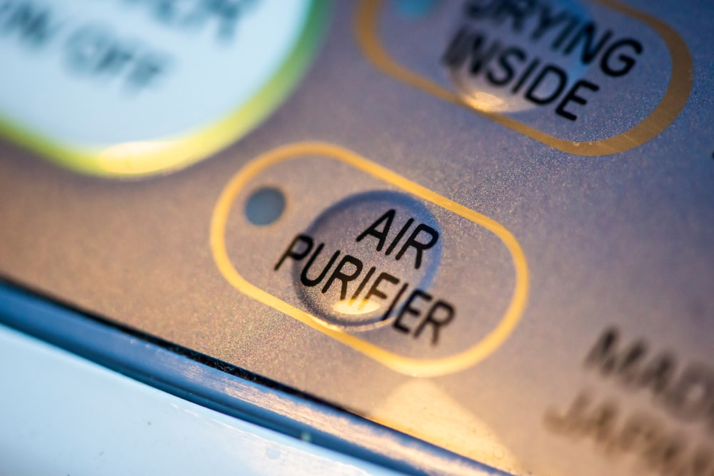 A close look at the control buttons of an appliance with an air purifier capability.
