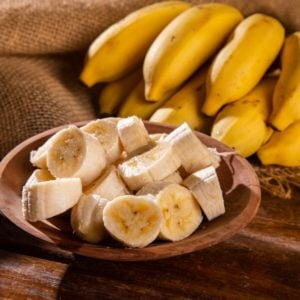 A bundle of ripe bananas with sliced bananas on a wooden bowl.