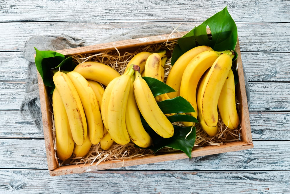 A few bundles of ripe bananas in a wooden crate.