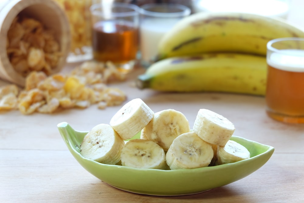 A close look at sliced bananas on a leaf-shaped saucer.