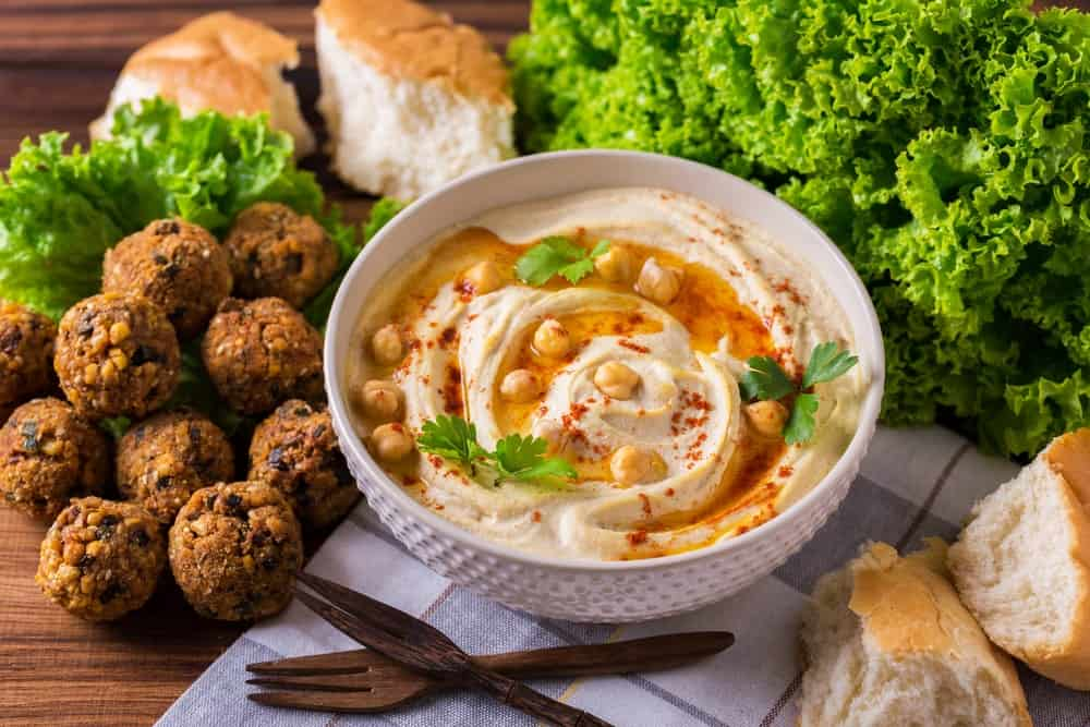 A bowl of hummus surrounded by lettuce, breads, and choco rolls.