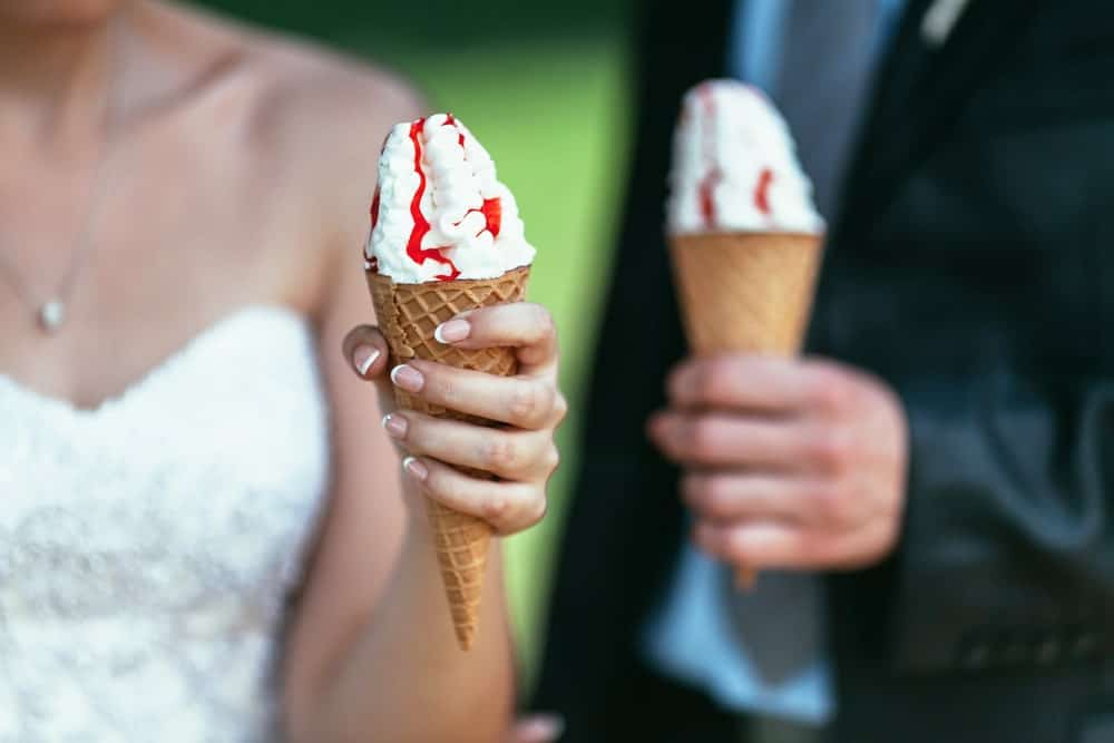 Newlywed couple holding an ice cream.