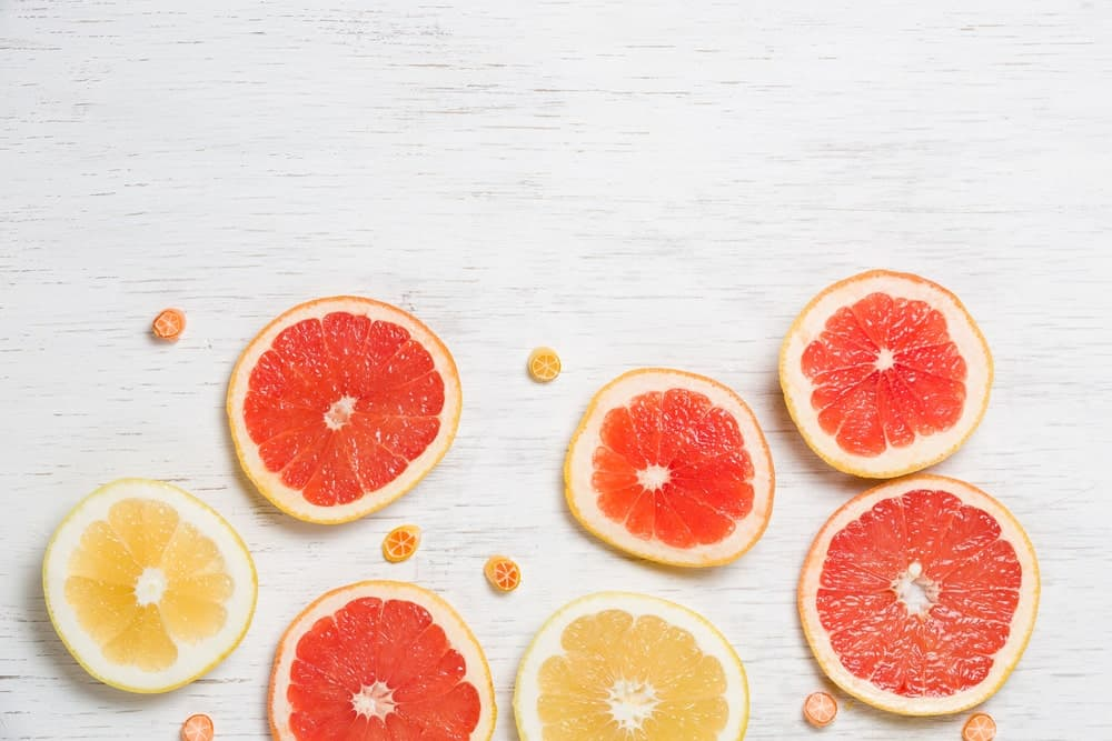 Slices of different types of grapefruits on white background.