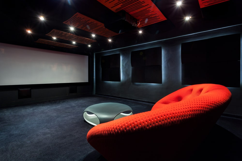 This is the spacious home theater with a red couch and a large white screen at the far end.