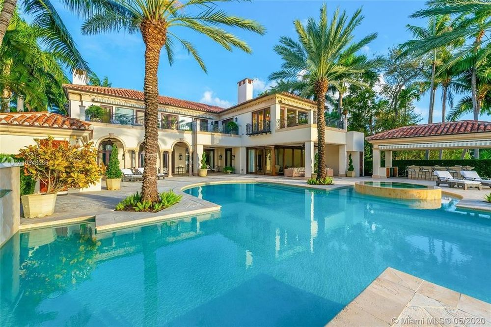 This is a look at the back of the mansion with a large swimming pool adorned by tall palm trees that bring color to the beige exteriors of the house with large windows. Image courtesy of Toptenrealestatedeals.com.