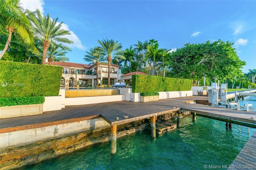 This is a look at the back of the house from the vantage of the wooden dock beyond the shrub hedges of the backyard. Image courtesy of Toptenrealestatedeals.com.