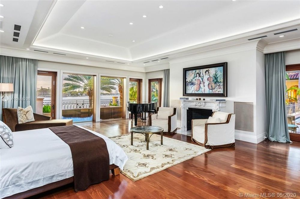 There is a sitting area across from the bed in this bedroom with a fireplace that is topped by a painting. Image courtesy of Toptenrealestatedeals.com.