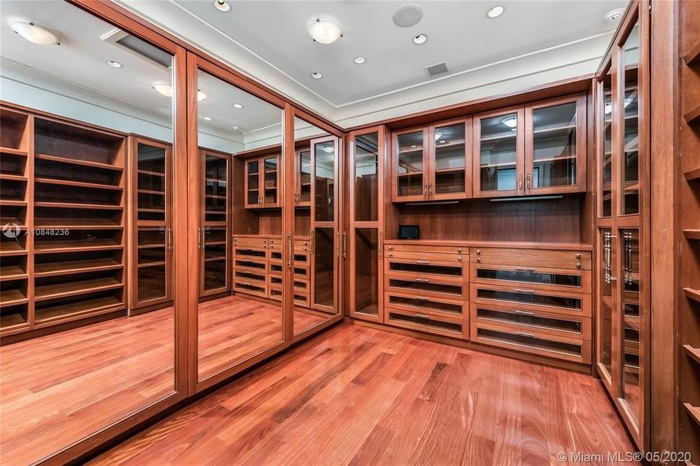 This is the wood-paneled walk-in closet with built-in cabinets, racks and shelves as well as large mirrors. Image courtesy of Toptenrealestatedeals.com.