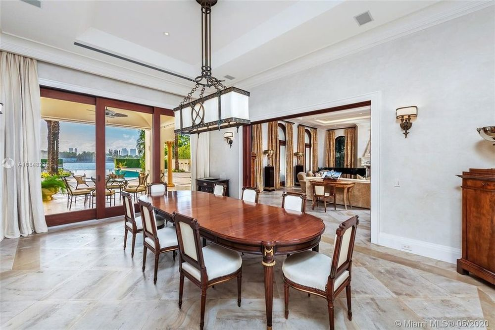 This is the formal dining room that has a long and dark wooden dining table surrounded by chairs with white cushions to match the lighting from the white tray ceiling. Image courtesy of Toptenrealestatedeals.com.