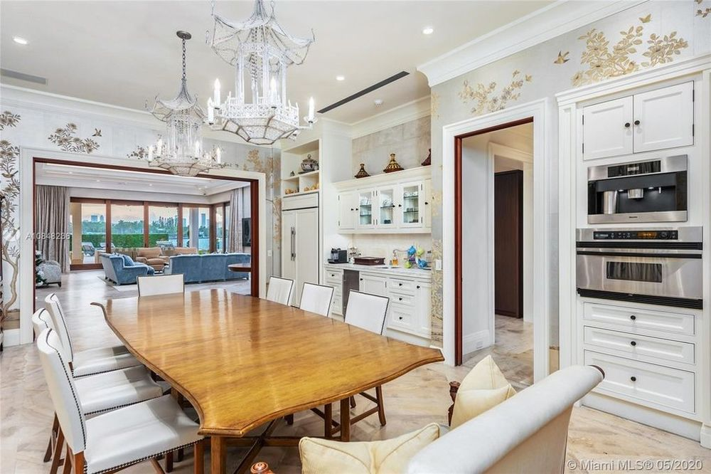 This is the other dining room with a large wooden dining table topped by crystal chandeliers. Image courtesy of Toptenrealestatedeals.com.