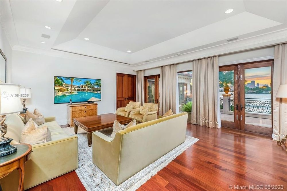 This is the family room with a dark hardwood flooring topped by the light area rug that complements the beige sofa set. Image courtesy of Toptenrealestatedeals.com.