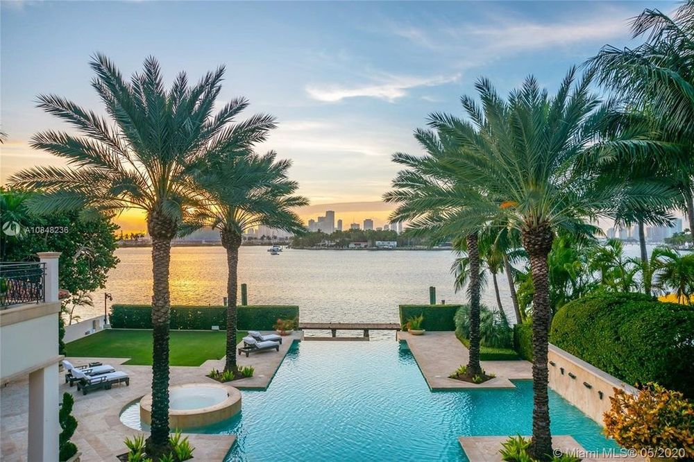 This is a look at the backyard swimming pool lined by tall palm trees. and low shrub hedges. Image courtesy of Toptenrealestatedeals.com.