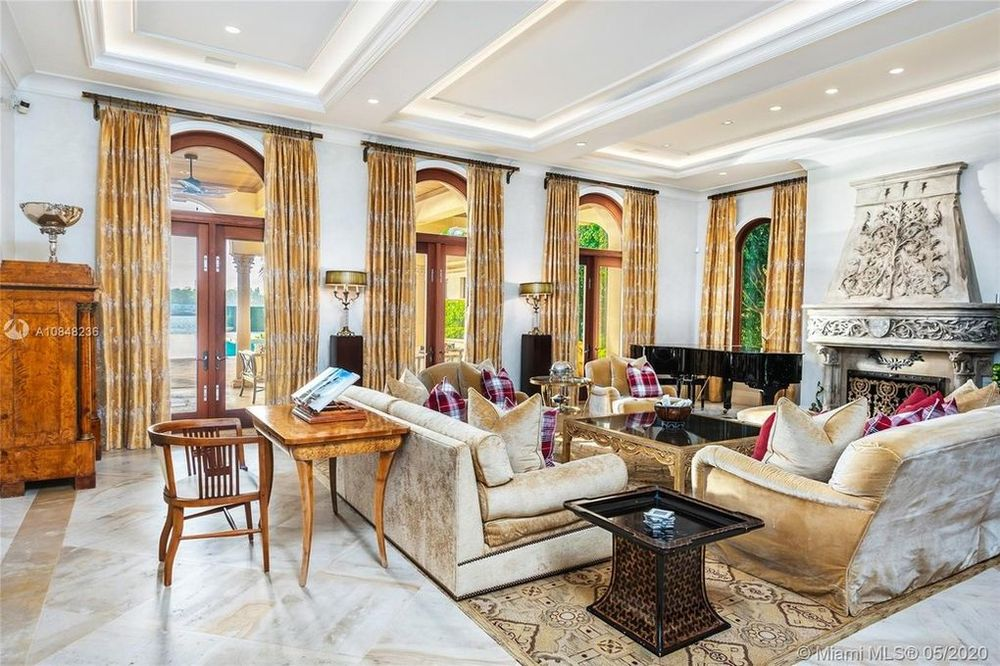 This is the bright and whiote living room with a beige sofas to match the curtains of the arched glass doors on one side. Image courtesy of Toptenrealestatedeals.com.