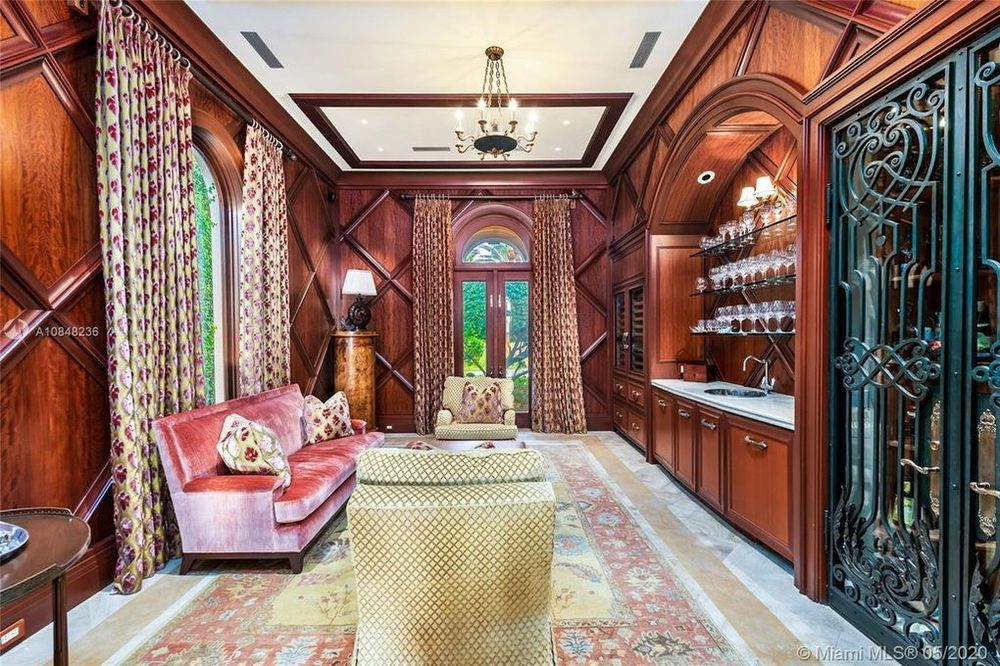 This is the a look at the wood-paneled wine room that has a sofa set paired with a wet bar and a large storage of wine bottles. Image courtesy of Toptenrealestatedeals.com.