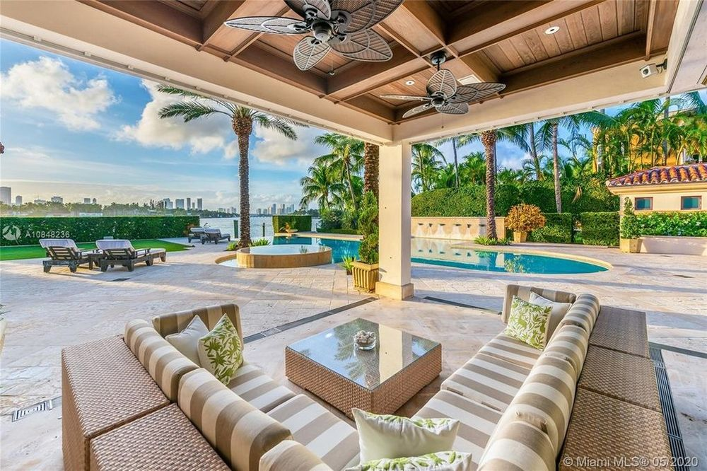 This is the covered patio by the poolside area. It has an L-shaped sectional sofa paired with a glass-top coffee table and a couple of ceiling fans. Image courtesy of Toptenrealestatedeals.com.