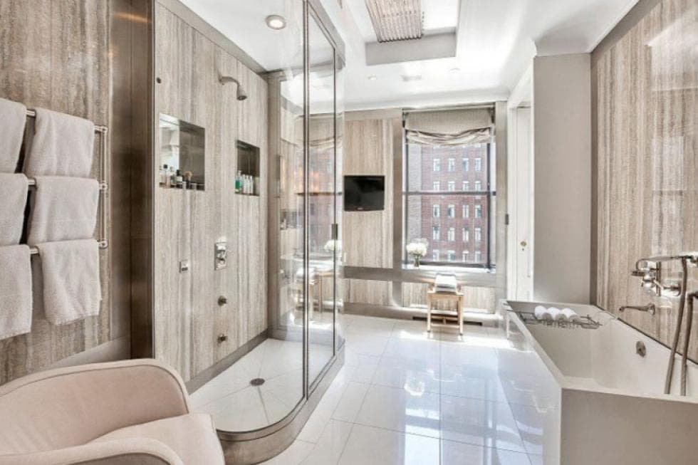 This is the bathroom with a glass-enclosed shower area in the middle across from the bathtub. Image courtesy of Toptenrealestatedeals.com.