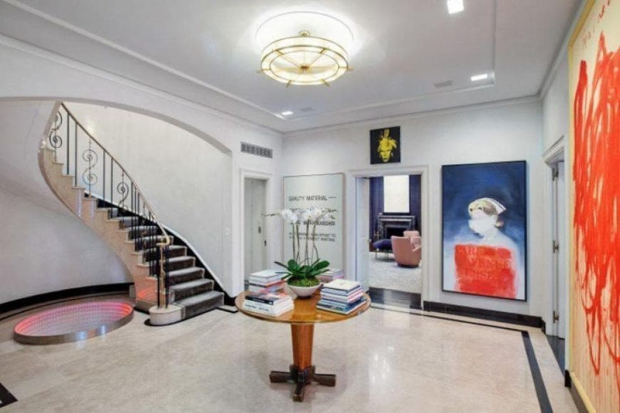 This is the foyer of the apartment with a curved staircase, a round wooden table topped with a flush-mount lighting and a colorful painting on the side. Image courtesy of Toptenrealestatedeals.com.
