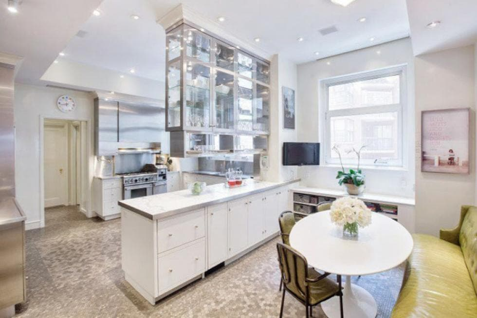 The white and bright kitchen has a peninsula that serves as a divider between the kitchen and the informal dining area that has a round table. Image courtesy of Toptenrealestatedeals.com.