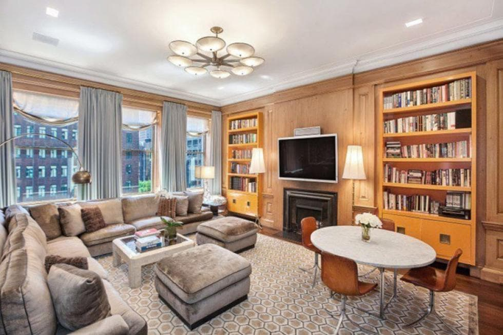 This is the library with wood panels on its walls that blend with the built-in bookshelves on either side of the fireplace across from the L-shaped sectional sofa. Image courtesy of Toptenrealestatedeals.com.