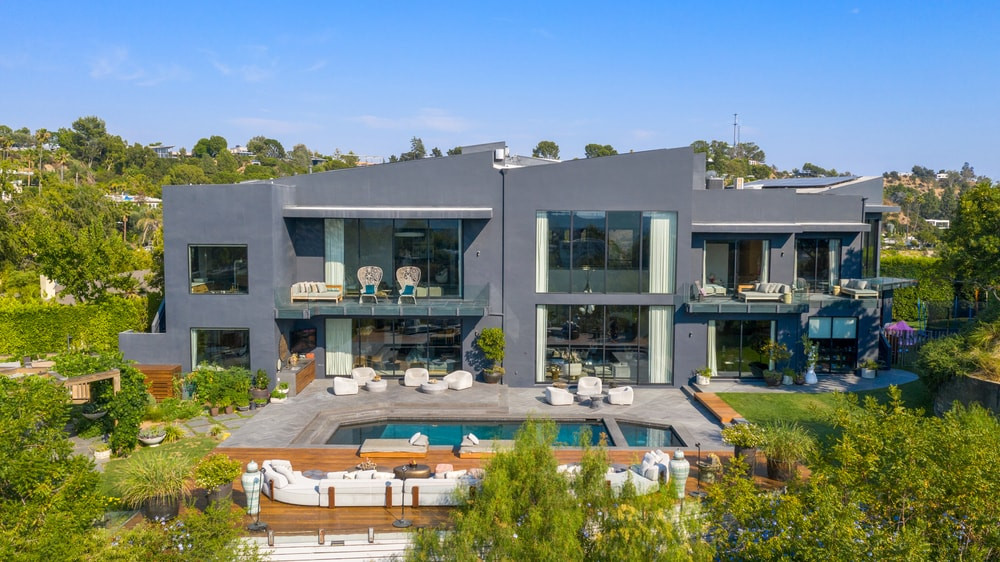 The back of the house has gray exterior walls adorned by large glass walls and windows as well as balconies. Image courtesy of Toptenrealestatedeals.com.