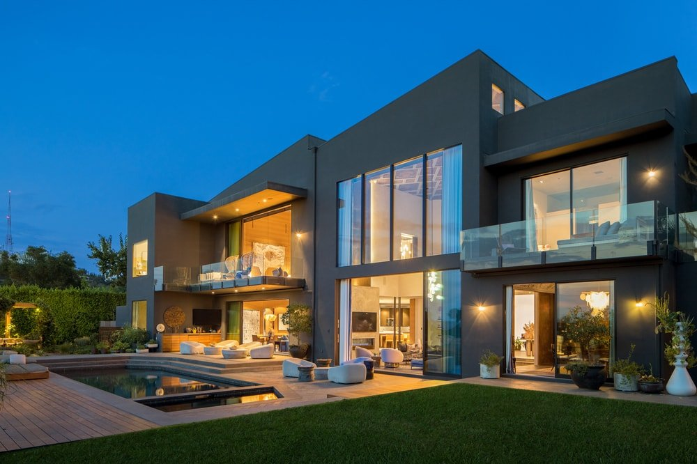 This is a nighttime view of the back of the house featuring the warm glow of the glass windows from the interior lights. Image courtesy of Toptenrealestatedeals.com.