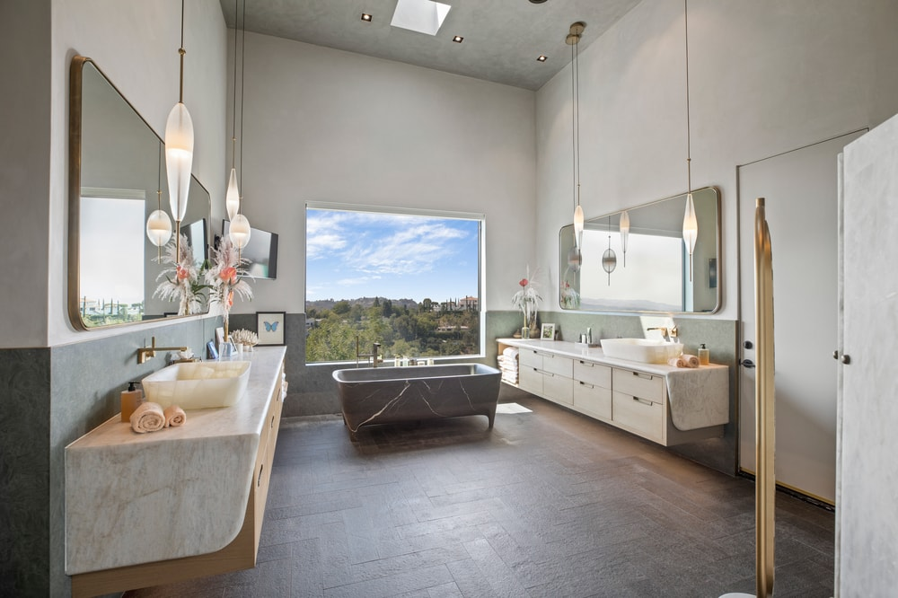 This is the primary bathroom with two vanities, a gray bathtub by the window and a walk-in shower area. Image courtesy of Toptenrealestatedeals.com.