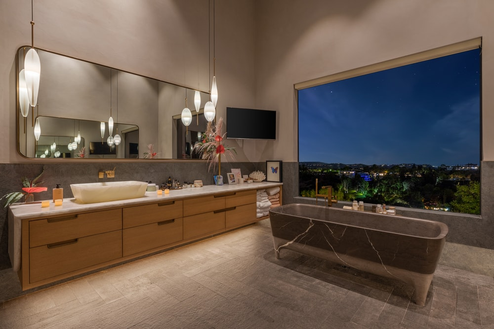 This is a nighttime view of the bathroom showcasing the large glass window above the bathtub that has a dark gray tone to stand out against the beige elements. Image courtesy of Toptenrealestatedeals.com.