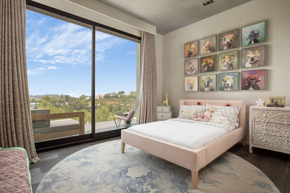 This is the children's bedroom with a pink bed, colorful wall-mounted decorations and a large set of glass doors that lead to the balcony. Image courtesy of Toptenrealestatedeals.com.