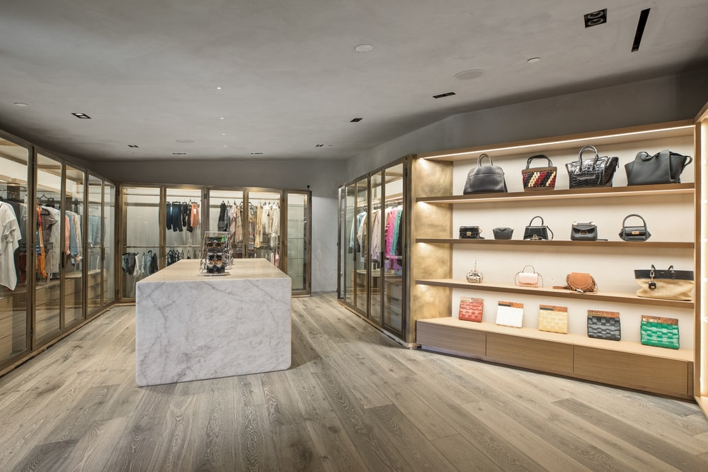 This is the walk-in closet with bags on lit shelves that are built into the walls and racks for clothes. Image courtesy of Toptenrealestatedeals.com.