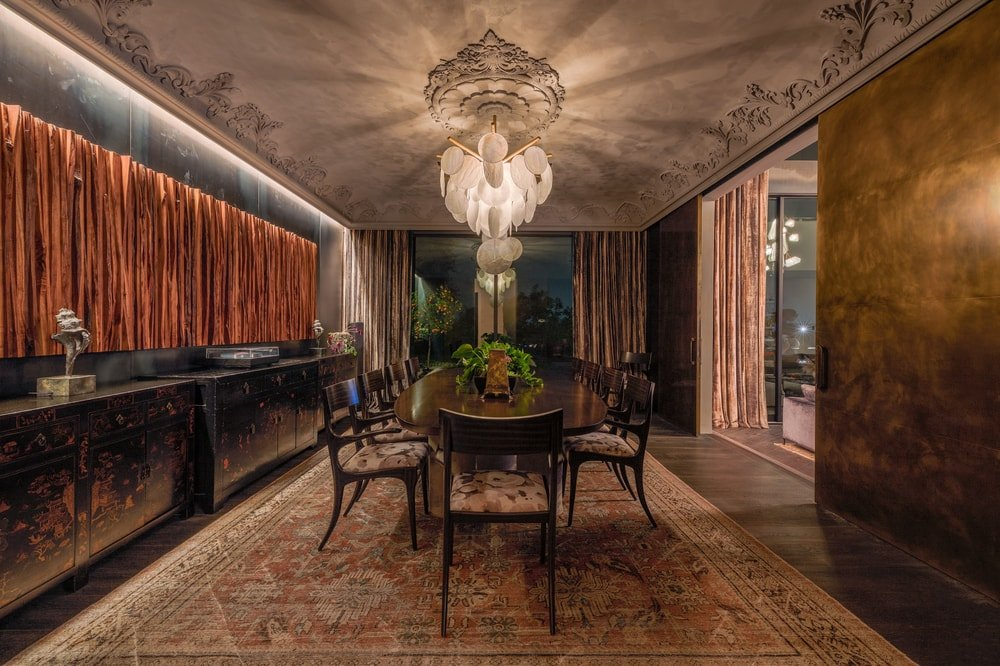 This is a closer look at the dining room with a large wooden dining table topped with a decorative lighting hanging from a detailed ceiling. Image courtesy of Toptenrealestatedeals.com.
