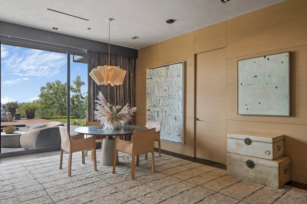 A few steps from the kitchen and family room is this corner that is fitted with a glass-top round table topped with a decorative lighting. Image courtesy of Toptenrealestatedeals.com.