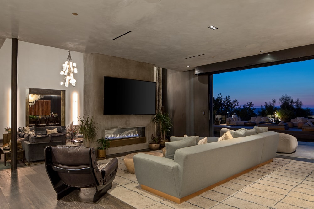 The sectional sofa of this family room is across from a large gray wall that houses a modern fireplace and a wall-mounted TV. Image courtesy of Toptenrealestatedeals.com.