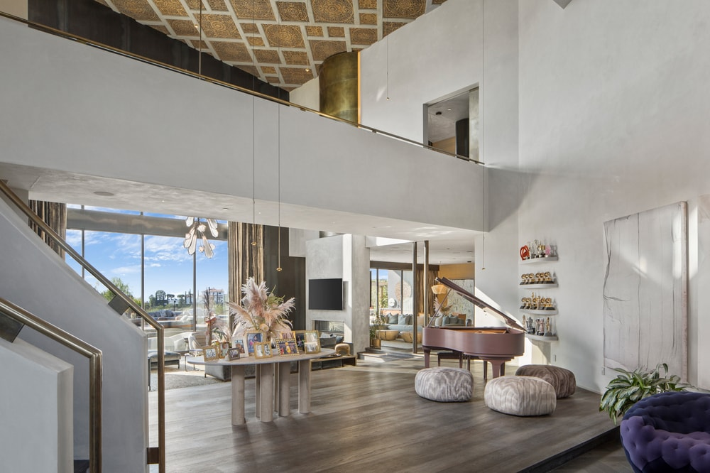 Upon entry of the house, you are welcomed by this foyer with a tall ceiling, an indoor balcony, a grand piano and a table in the middle bearing flowers. Image courtesy of Toptenrealestatedeals.com.